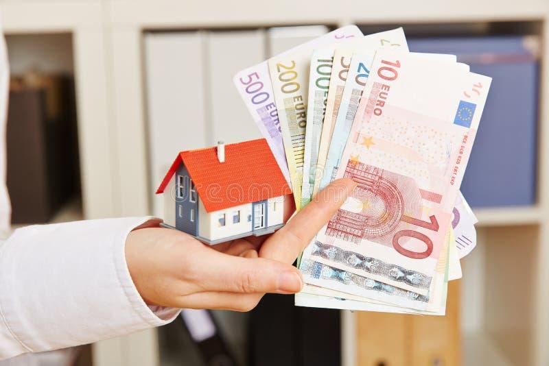 Mão que guarda a casa e o dinheiro do Euro fotografia de stock