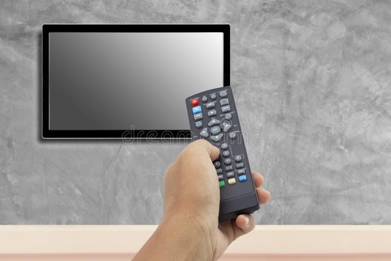 Mão que guarda de controle remoto na tela da televisão imagens de stock royalty free