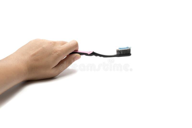 Mão que guarda a escova de dentes e o toothpast imagens de stock