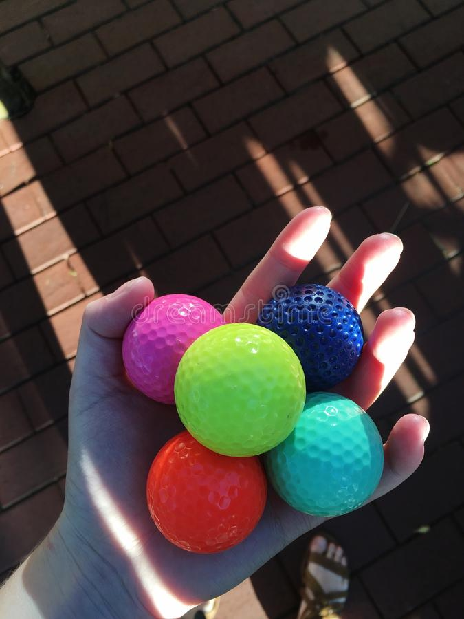 Mão que guarda golfballs coloridos foto de stock royalty free