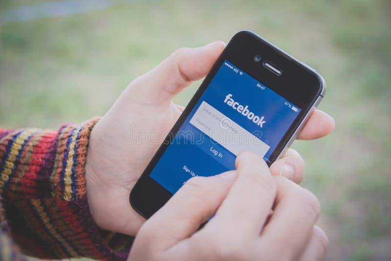 Mão que guarda Iphone e que usa a aplicação de Facebook fotografia de stock royalty free
