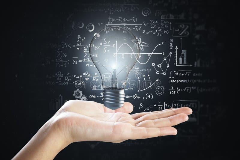 Mão que guarda a lâmpada com fórmulas fotografia de stock