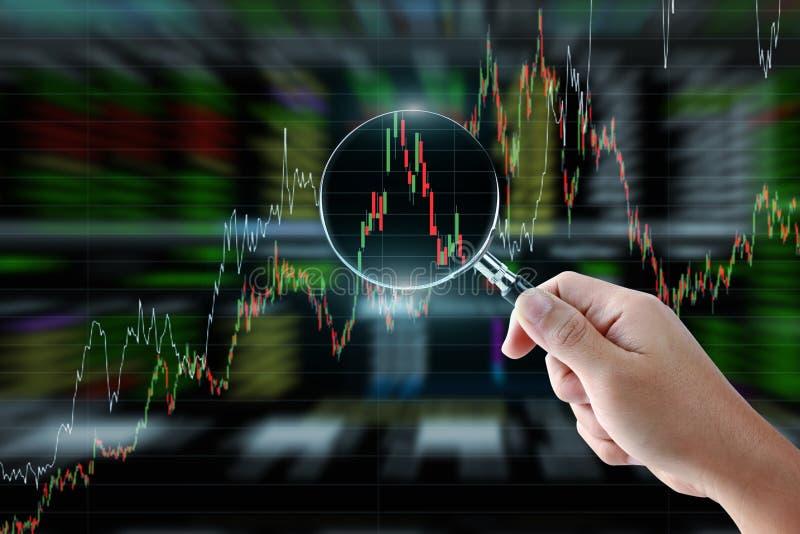 Mão que guarda a lupa com gráfico do mercado de valores de ação ilustração royalty free