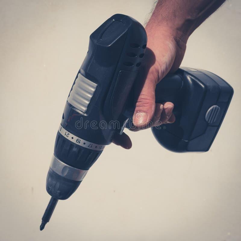 Mão que guarda a máquina de perfuração, chave de fenda elétrica fotografia de stock