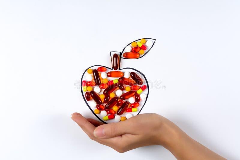 Mão que guarda a maçã de tiragem com cápsulas e os comprimidos coloridos no fundo branco Vitaminas dos cuidados médicos ou concei imagem de stock royalty free