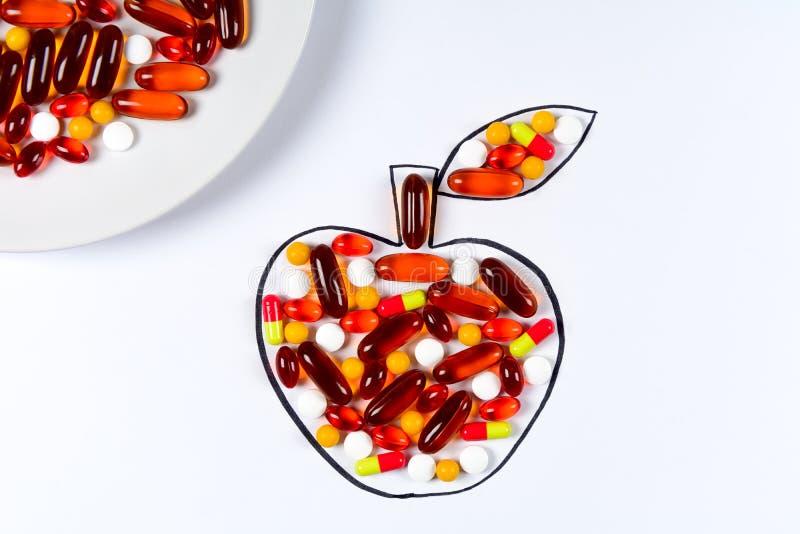 Mão que guarda a maçã de tiragem com cápsulas e os comprimidos coloridos no fundo branco Vitaminas dos cuidados médicos ou concei fotos de stock