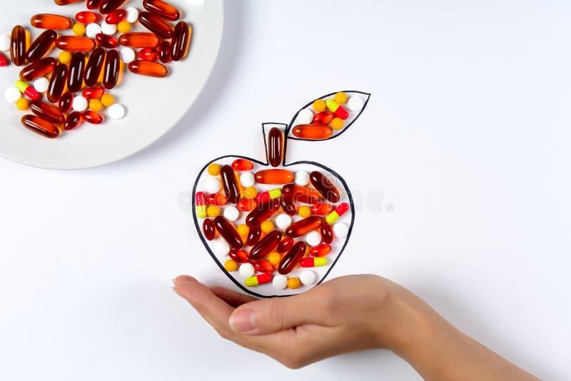 Mão que guarda a maçã de tiragem com cápsulas e os comprimidos coloridos no fundo branco Vitaminas dos cuidados médicos ou concei foto de stock royalty free