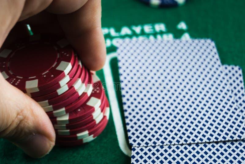 Mão que guarda microplaquetas de pôquer fotos de stock