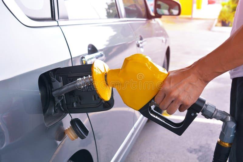 Mão que guarda o bocal de combustível para adicionar o gás fotografia de stock