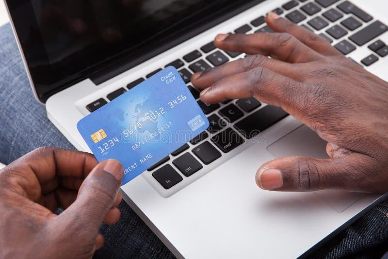 Mão que guarda o cartão de crédito com portátil fotografia de stock