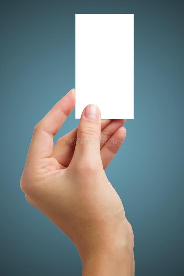 A mão que guarda o cartão vazio branco da visita do negócio, presente, bilhete, passagem, apresenta isolado no fundo azul Copie o fotos de stock