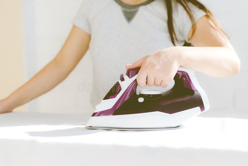 Mão que guarda o close-up do ferro, menina que afaga a camisa branca da roupa em um fundo claro fotografia de stock