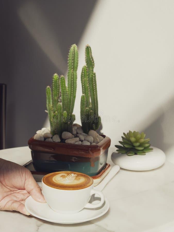 Mão que guarda o copo de café do latte ou da arte do cappuccino na tabela com luz solar no café imagem de stock royalty free