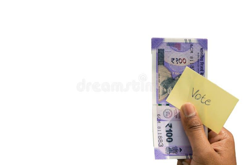 Mão que guarda o dinheiro e para votar um conceito da corrupção política a compra dos votos nas eleições no fundo isolado foto de stock