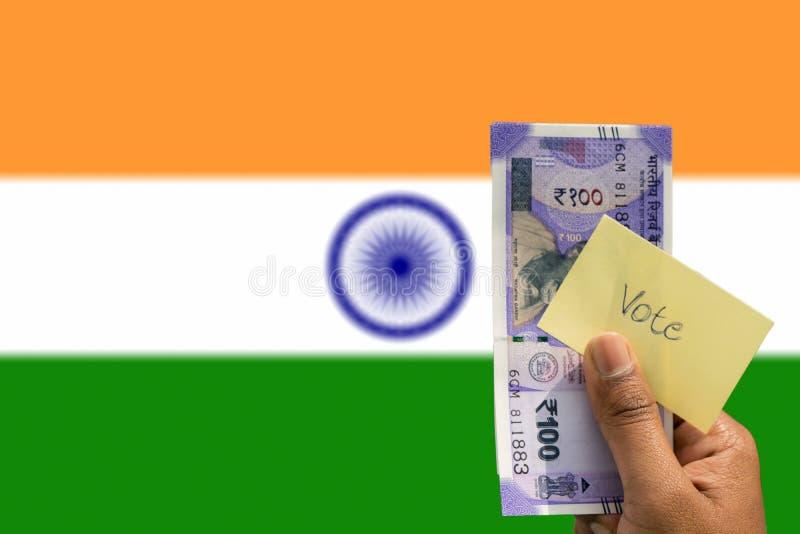 Mão que guarda o dinheiro e para votar um conceito da corrupção política a compra dos votos no fundo das eleições como um indiano fotos de stock