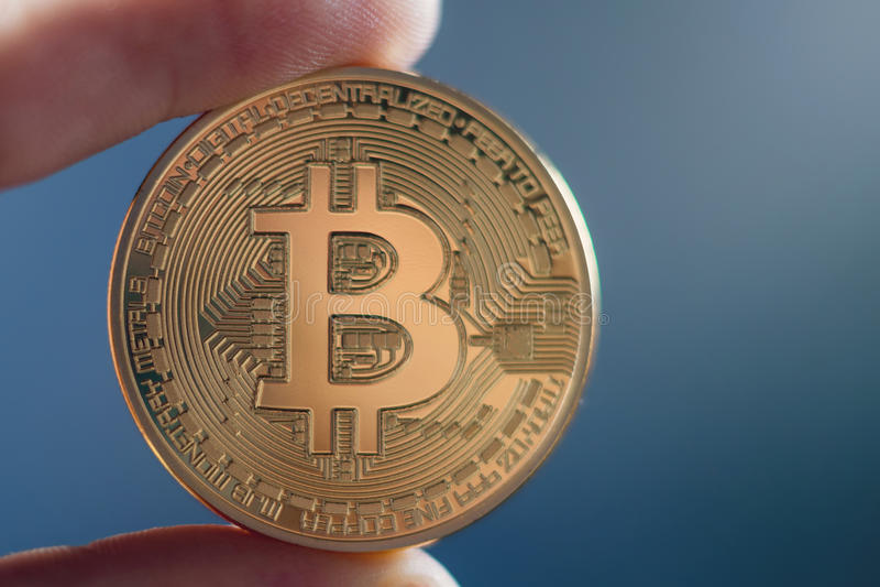 Mão que guarda o dinheiro virtual dourado de Bitcoin fotografia de stock