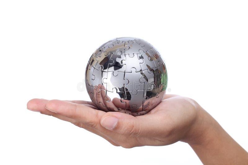 Mão que guarda o globo do enigma do metal imagens de stock royalty free