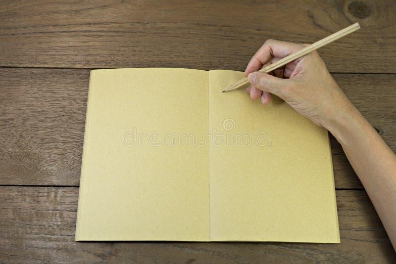 Mão que guarda o lápis no caderno imagens de stock