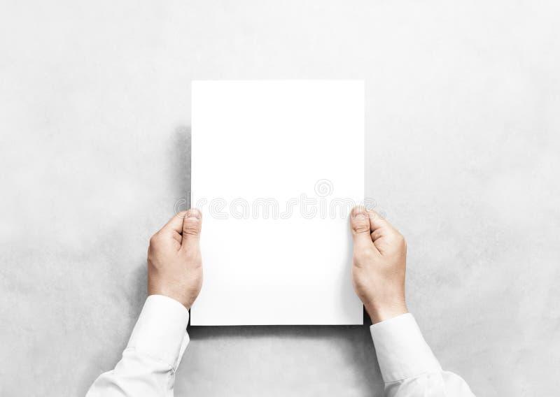Mão que guarda o modelo branco da folha do papel vazio, imagem de stock