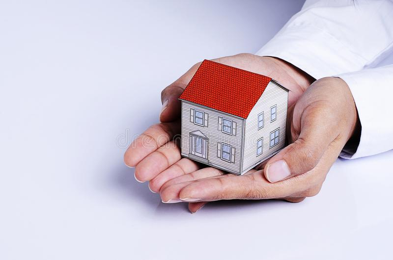 Mão que guarda o papel da casa para o conceito dos empréstimos hipotecários fotografia de stock royalty free