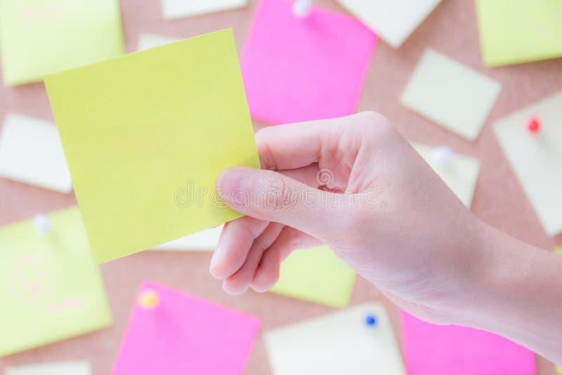 Mão que guarda o papel vazio do post-it foto de stock
