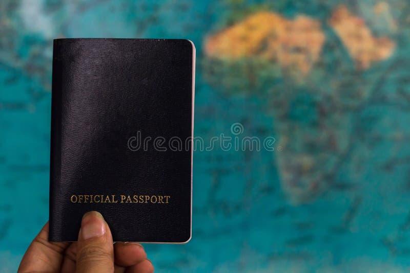 Mão que guarda o passaporte com fundo do mapa imagem de stock
