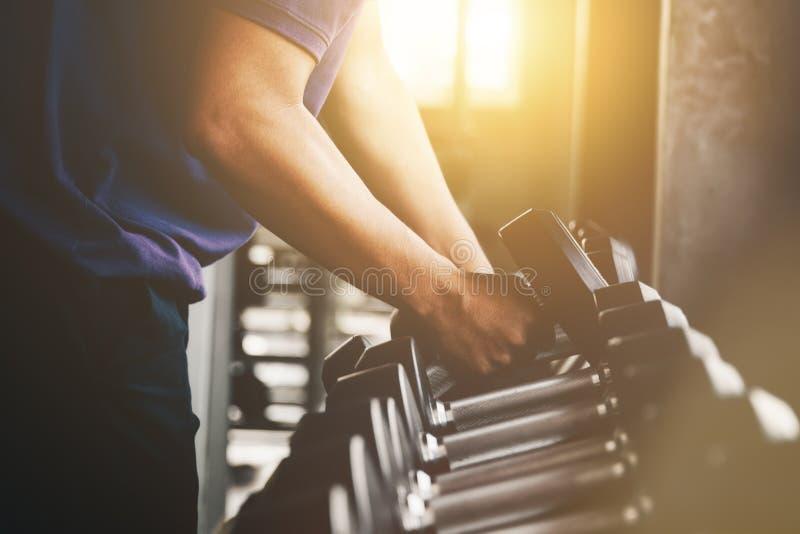 Mão que guarda o peso do peso no fim do gym acima do exercício do músculo do braço com peso do metal fotos de stock