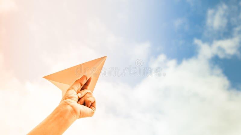 Mão que guarda o plano de papel no fundo do céu fotografia de stock royalty free
