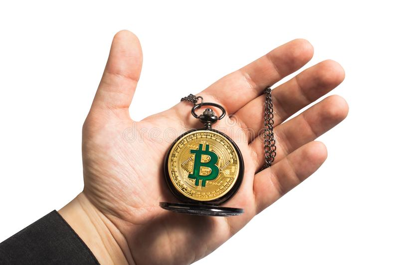Mão que guarda o relógio do bitcoin fotografia de stock royalty free
