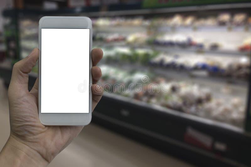Mão que guarda o smartphone com a tela vazia branca sobre o sup borrado foto de stock royalty free