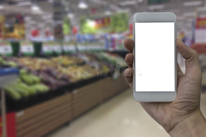 Mão que guarda o smartphone com a tela vazia branca sobre o sup borrado fotos de stock
