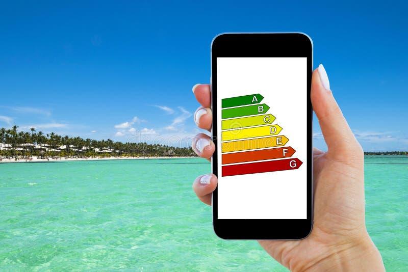 M?o que guarda o smartphone digital com avalia??o de efici?ncia da casa Detalhe de avalia??o de efici?ncia da casa na tela digita imagem de stock