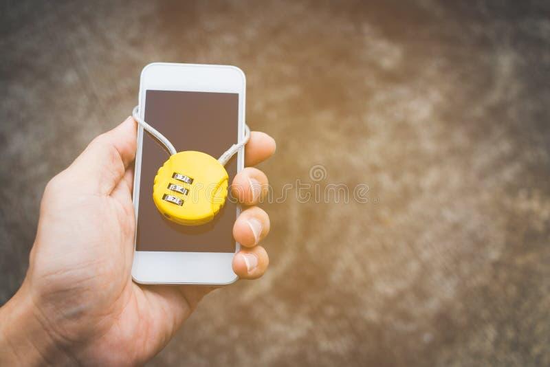 Mão que guarda o smartphone fechado com cadeado fotografia de stock