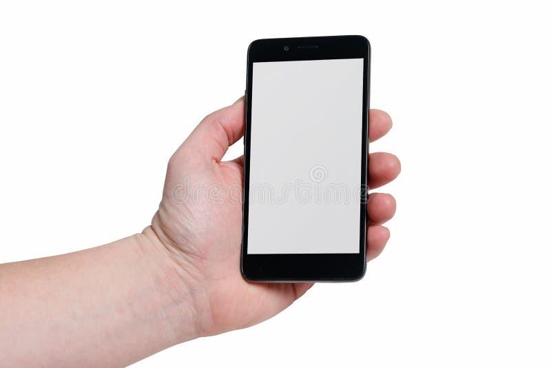 Mão que guarda o smartphone preto com tela vazia e quadro moderno menos projeto - isolado no fundo branco imagens de stock royalty free