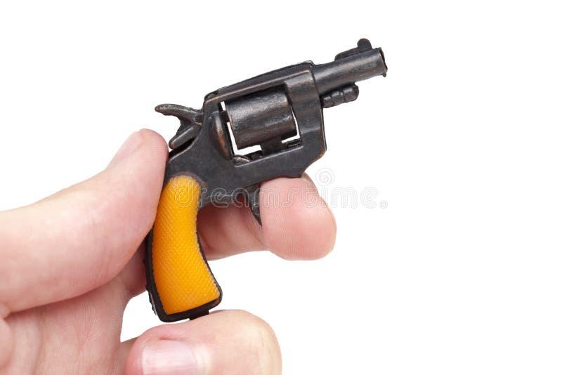 M?o que guarda o suporte min?sculo pequeno da arma do brinquedo que puxa o disparador isolado no fundo branco foto de stock