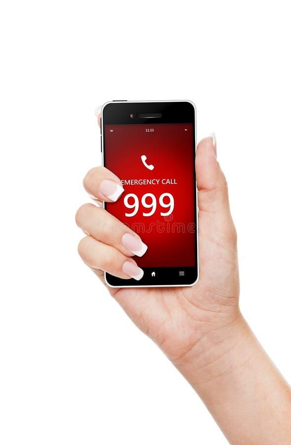 Mão que guarda o telefone celular com emergência número 999 foto de stock royalty free