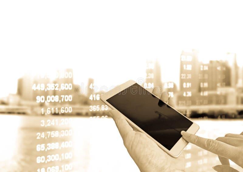 Mão que guarda o telefone esperto na cotação das ações fotografia de stock