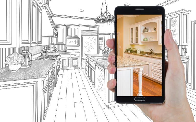 Mão que guarda o telefone esperto que indica a foto da cozinha que tira Beh imagens de stock