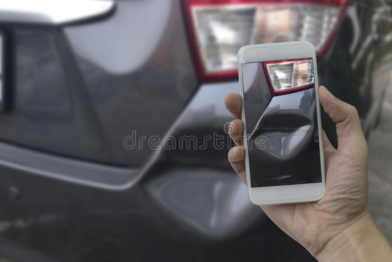 A mão que guarda o telefone esperto toma uma foto na cena de cras de um carro imagens de stock royalty free