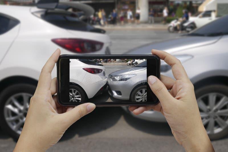 A mão que guarda o telefone esperto toma uma foto na cena de cras de um carro fotos de stock