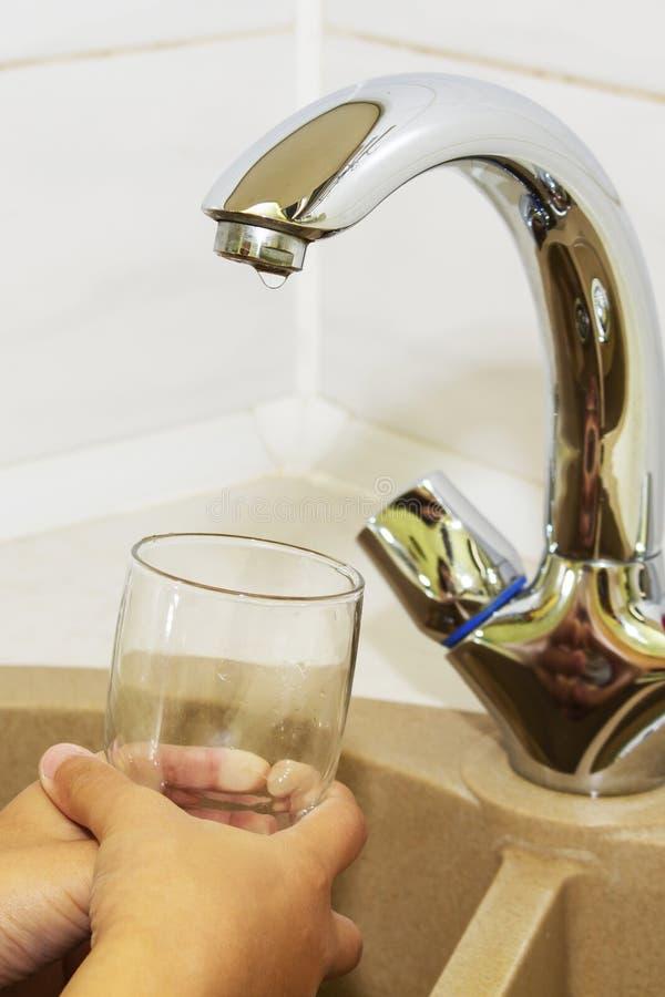 A mão que guarda o vidro e que espera quando a água será fotografia de stock