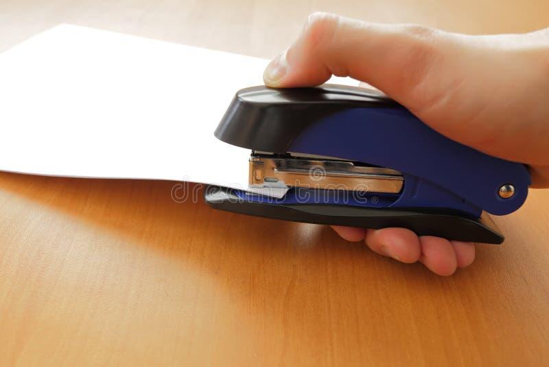 Mão que guarda papéis grampeando do grampeador azul fotos de stock royalty free