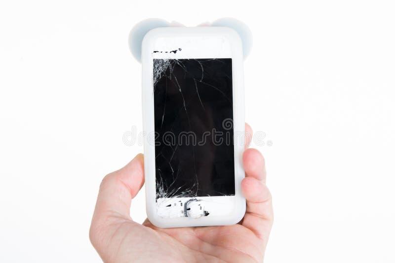 Mão que guarda para fora seu telefone celular quebrado do tela táctil imagens de stock royalty free