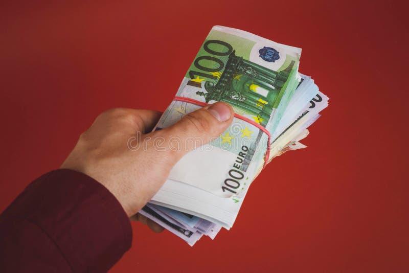 mão que guarda para fora uma pilha de dinheiro em um fundo vermelho imagens de stock royalty free