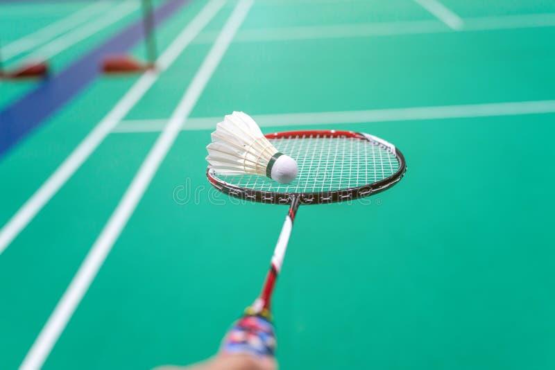 mão que guarda a peteca do badminton com a raquete na corte fotografia de stock