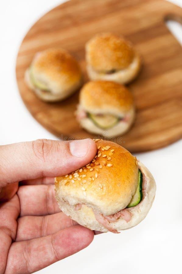 Mão que guarda sanduíches do Hamburger foto de stock
