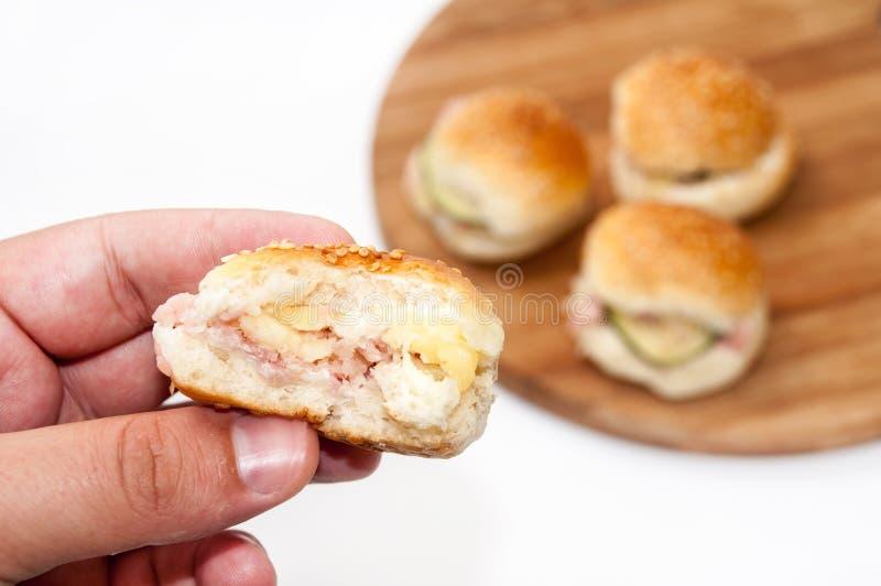 Mão que guarda sanduíches do Hamburger imagem de stock royalty free