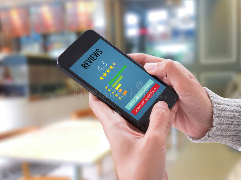 Mão que guarda a satisfação do cliente esperta da verificação da revisão do telefone foto de stock royalty free
