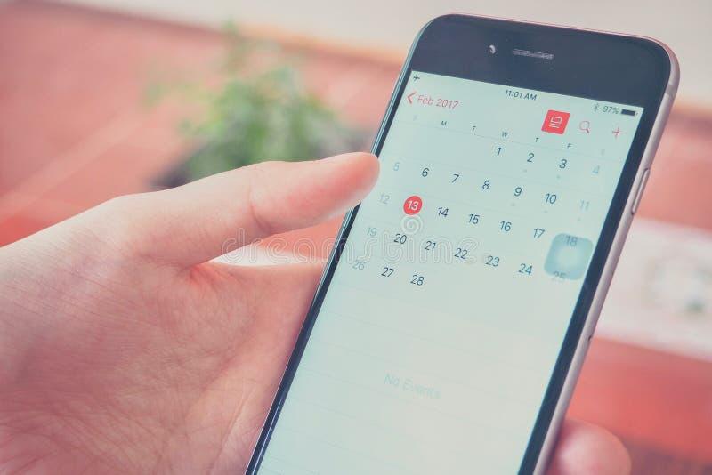 Mão que guarda Smartphone ao olhar o calendário foto de stock royalty free