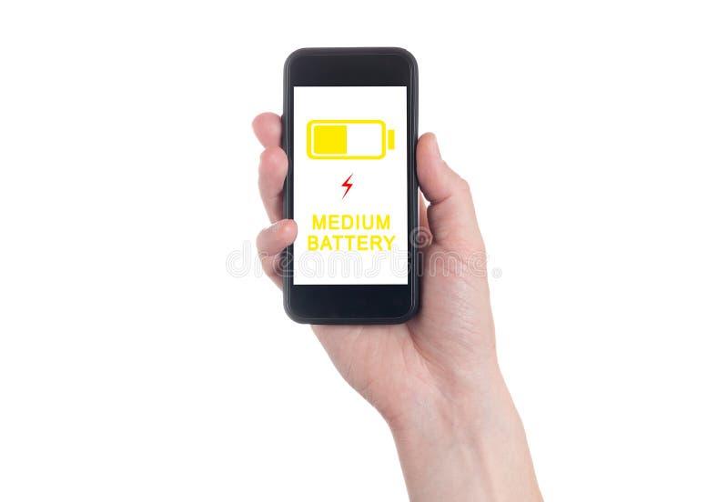 Mão que guarda Smartphone preto com a tela vazia no backgroun branco Indicador de carga da bateria Bateria nivelada de carregamen foto de stock royalty free